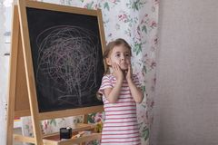 Child is drawing with pieces of color chalk on the chalk board. Girl is expressing creativity and looking at the camera. Child is drawing with pieces of color royalty free stock photos