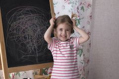 Child is drawing with pieces of color chalk on the chalk board. Girl is expressing creativity and looking at the camera. Child is drawing with pieces of color royalty free stock photo