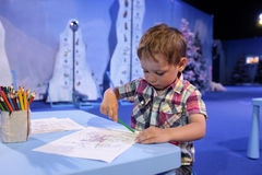 Child drawing in playroom. The child drawing in the blue playroom royalty free stock photo