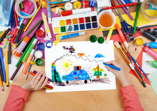Child drawing police car and helicopter, top view hands with pencil painting picture on paper, artwork workplace Royalty Free Stock Photography