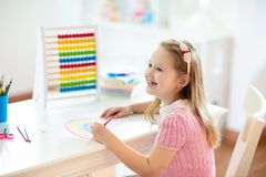 Child drawing. Kids paint. Girl after school. Child drawing rainbow. Kid painting at home. Little girl doing homework after school. Kids desk with abacus in royalty free stock photos