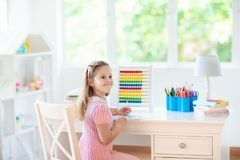 Child drawing. Kids paint. Girl after school. Child drawing rainbow. Kid painting at home. Little girl doing homework after school. Kids desk with abacus in royalty free stock photography