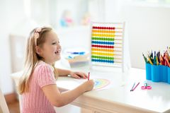 Child drawing. Kids paint. Girl after school. Child drawing rainbow. Kid painting at home. Little girl doing homework after school. Kids desk with abacus in stock image