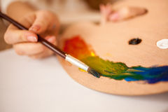 Child drawing rainbow by oil paint on wooden pallet Stock Photo