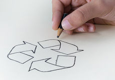 A child drawing the recycling symbol with a very short pencil st Stock Image