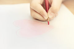 Child is drawing red heart. By pencil royalty free stock images