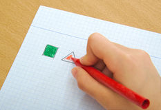 Child drawing red triangle and green square with Stock Image