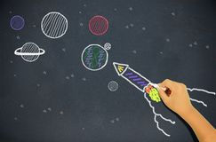 Child drawing a rocket. On a blackboard with planets in background stock images