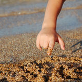 Child drawing on sand Royalty Free Stock Images