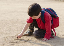 Child drawing into sand stock image