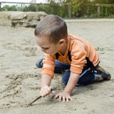 Child drawing into sand Stock Images