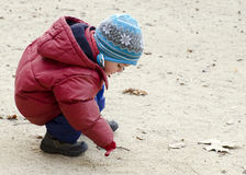 Child drawing into sand. With a stick in a park on a cold autumn or fall or winter day stock photos