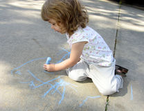 Child drawing on sidewalk stock photos