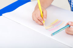 Child drawing. Child sitting at the table and drawing by colour pencil royalty free stock photo