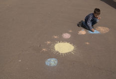 The child drawing space and planets Royalty Free Stock Photo