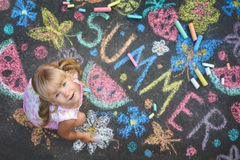 Child drawing summer spirit on asphalt