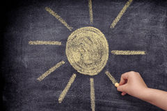 Child drawing sun with chalk. Close up stock image