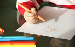 Child drawing a sun with colorful markers. Child drawing a smiling sun with colorful markers close up hands royalty free stock photography