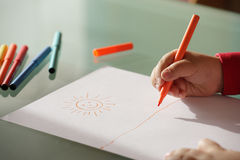 Child drawing  a sun  with colorful markers Royalty Free Stock Images