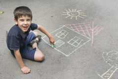 Child drawing sun and house on asphal Royalty Free Stock Images