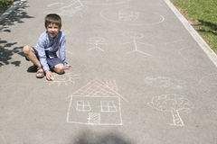 Child drawing sun and house on asphal Stock Photo