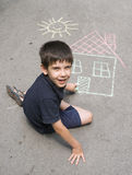 Child drawing sun and house on asphal royalty free stock image