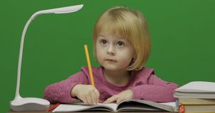 Child drawing at the table. Education process in classroom. Chroma Key stock photos