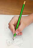 Child drawing teddy bears. And heart with grey pencil Royalty Free Stock Image