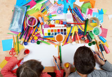 Child drawing top view. Artwork workplace with creative accessories. Flat lay art tools for painting. Stock Photo