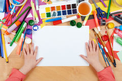 Child drawing top view. Artwork workplace with creative accessories. Flat lay art tools for painting. Stock Photos