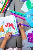 Child drawing. Top view of child hands with pencil painting picture on paper. Kid drawings. Child drawing. Top view of child hands with pencil painting picture royalty free stock image
