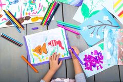 Child drawing. Top view of child hands with pencil painting picture on paper. Kid drawings. Child drawing. Top view of child hands with pencil painting picture stock images