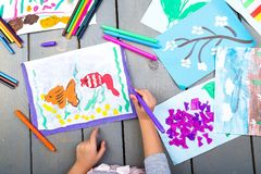 Child drawing. Top view of child hands with pencil painting picture on paper. Kid drawings. Child drawing. Top view of child hands with pencil painting picture royalty free stock photos