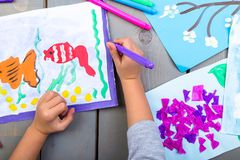 Child drawing. Top view of child hands with pencil painting picture on paper. Kid drawings. Child drawing. Top view of child hands with pencil painting picture stock photo