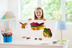Child drawing unicorn using tree leaves. Kid painting pony or horse at home. Little girl doing homework after school. Kids crafts and art. Children paint. Arts royalty free stock photos