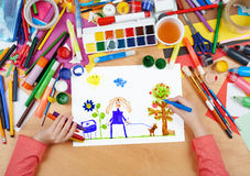 Child drawing walking girl with dog, top view hands with pencil painting picture on paper, artwork workplace Royalty Free Stock Photography