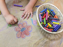 Child drawing with wax crayons over wrapping Royalty Free Stock Images