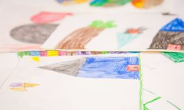 Child drawings. With colored pencils, stacked on table, on wire stock image