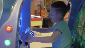 Boy having fun with sea-battle arcade. Child with drawn cat face entertaining in amusement park and playing sea-battle video game stock video footage