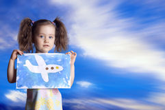 The child with the drawn plane against the sky Stock Photos