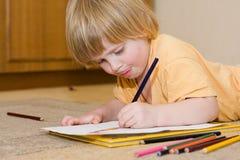 Child draws. Little girl studies to draw Stock Image