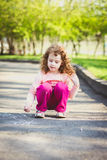 Child draws on asphalt in the park. Royalty Free Stock Photo