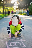 Child draws on asphalt. Selective focus. Little boy draws on asphalt. Selective focus royalty free stock photo