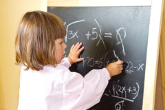 Child draws with chalk on the blackboard Stock Images