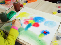The child draws. Children's hand holding a brush and paints wet on wet Stock Photos