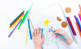 The child draws a Christmas tree with colored pencils and marker. A boy draws a Christmas tree in a notebook. Color markers. White background Royalty Free Stock Photo