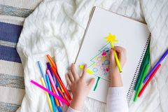 The child draws a Christmas tree with colored pencils and marker. A boy draws a Christmas tree in a notebook. Color markers. White background Royalty Free Stock Photography