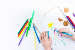 The child draws a Christmas tree with colored pencils and marker. A boy draws a Christmas tree in a notebook. Color markers. White background Royalty Free Stock Images