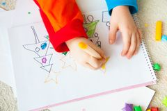 The child draws a Christmas tree with markers and colored pencil. A boy draws a Christmas tree. Child`s drawing Christmas. The child lies on the floor and draws Royalty Free Stock Image
