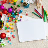 The child draws a Christmas tree with markers and colored pencil. A boy draws a Christmas tree. Child`s drawing Christmas. The child lies on the floor and draws Royalty Free Stock Photo